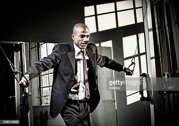 Businessman in fitness lifting weights