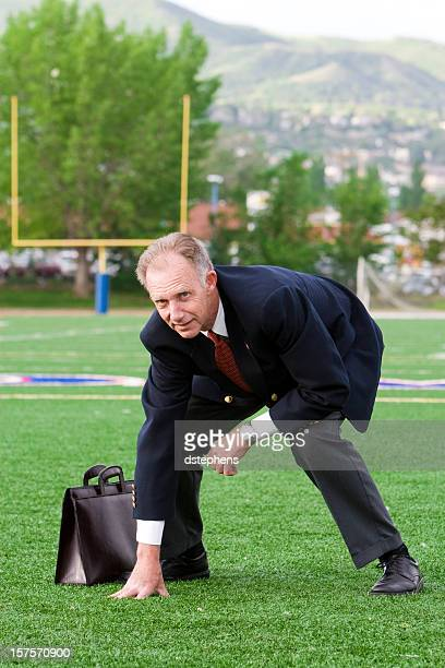 Businessman in football stance