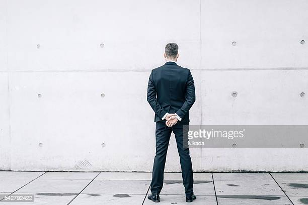 Businessman in front of a concrete wall