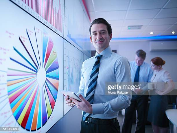 Businessman in front of graphs on screen in meeting room