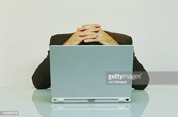 Businessman in front of laptop with head down