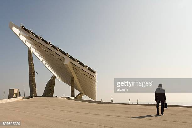 Businessman in front of modern solar panel