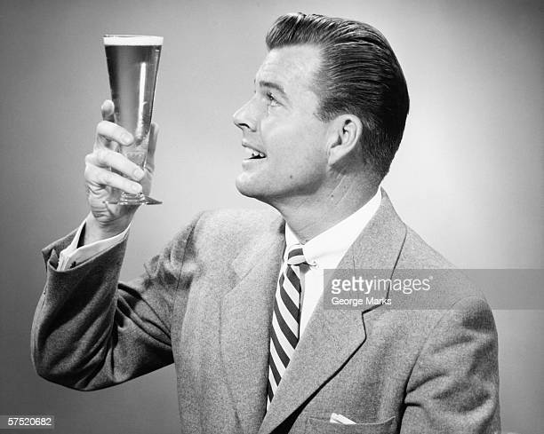 Businessman in full suit in studio holding glass of beer, (B&W)