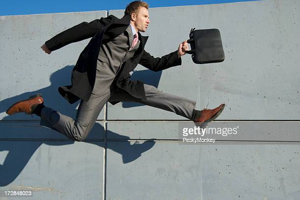 Businessman in Full Suit Jumping Outdoors Gray Wall Background