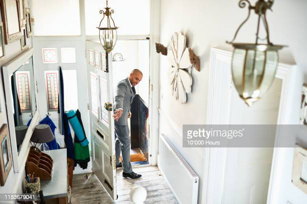 businessman in grey suit closing front door - leaving stock pictures, royalty-free photos & images