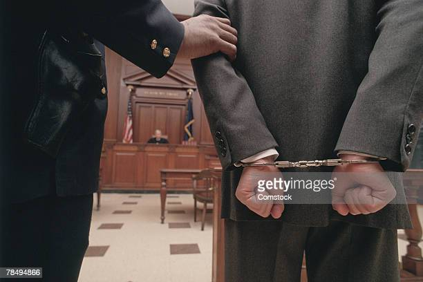businessman in handcuffs in courtroom - crime or recreational drug or prison or legal trial stock-fotos und bilder