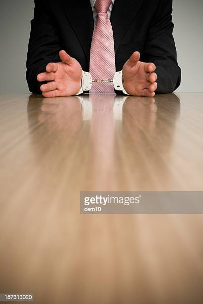 Businessman in handcuffs sitting at table