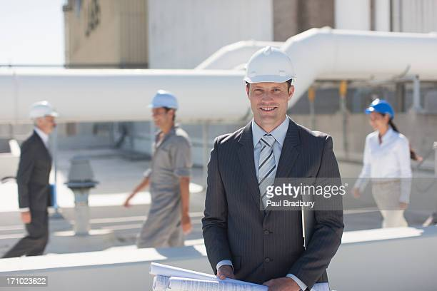 Businessman in hard-hat holding blueprints outdoors