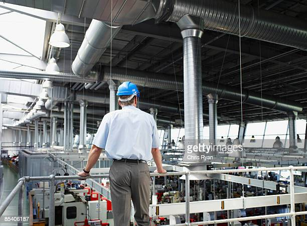Businessman in hard-hat looking at factory floor