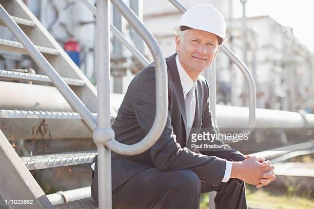 Geschäftsmann in harten-Mütze sitzt auf industriellen Schritte