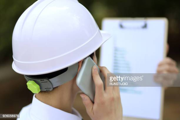 Businessman in hardhat talking on smartphone with clipboard outdoors
