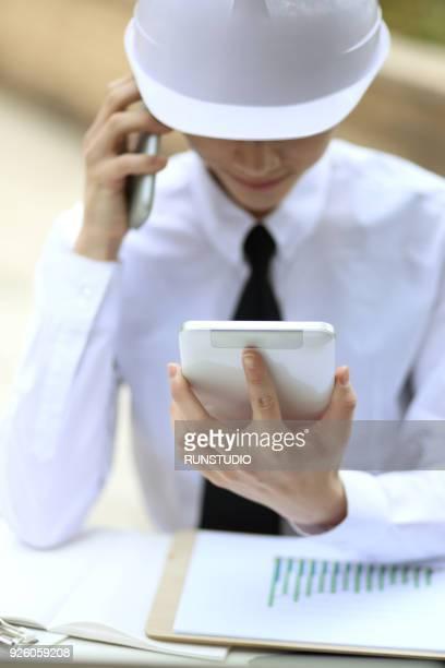 Businessman in hardhat  talking on smartphone with digital tablet