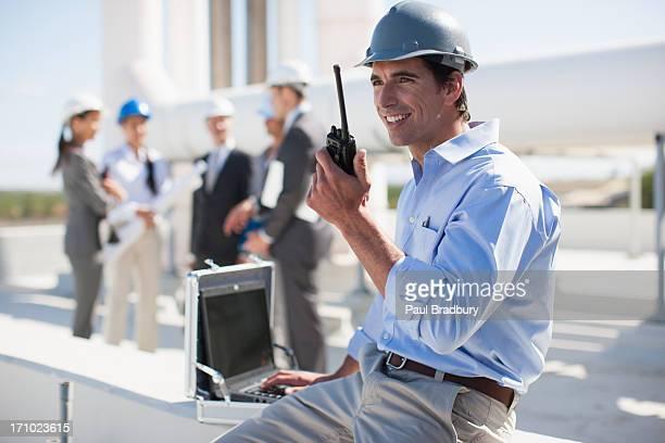Homme d'affaires dans le chapeau dur parler sur talkie-walkie en plein air
