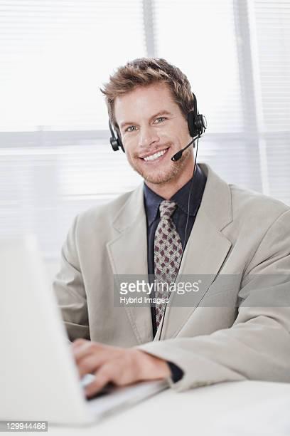 ビジネスマンのヘッドセットノートパソコンを使う