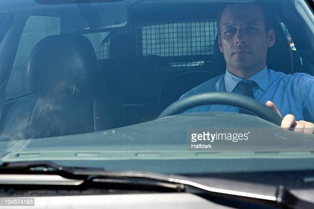 A businessman in his car, looking through windshield
