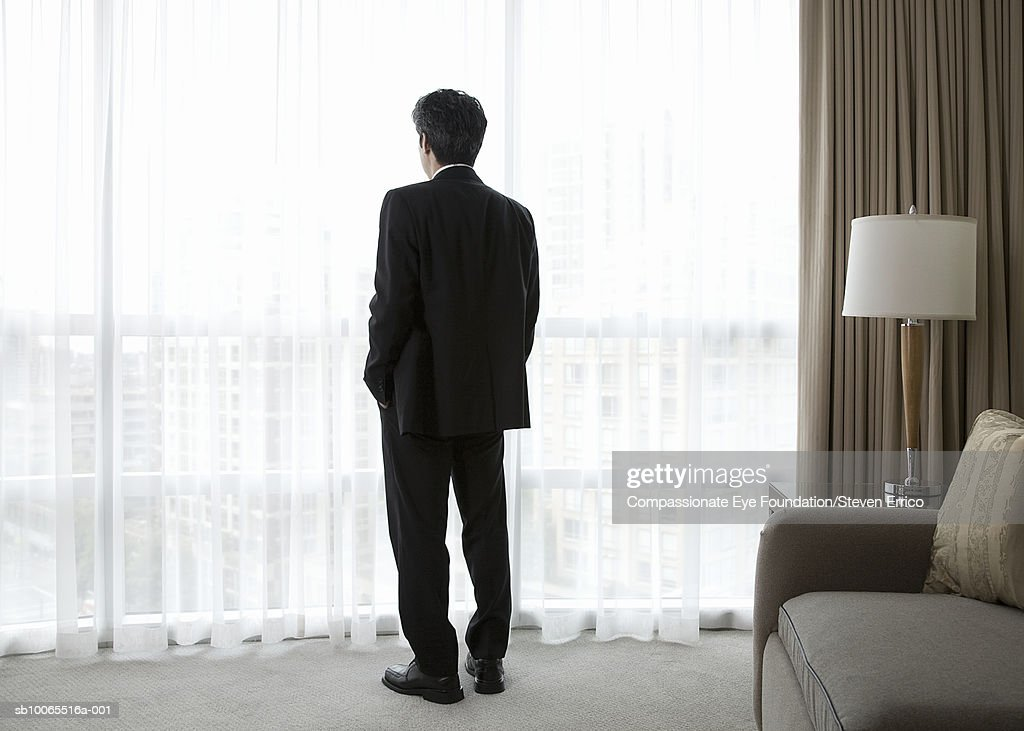 Businessman in hotel room, looking out window, rear view : Stock-Foto