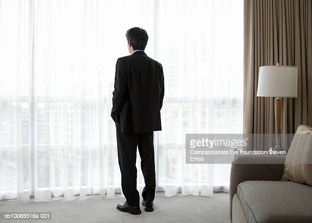 Businessman in hotel room, looking out window, rear view