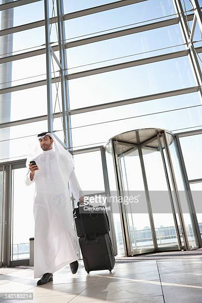businessman in kaffiyeh with suitcase in lobby - traditional clothing stock pictures, royalty-free photos & images