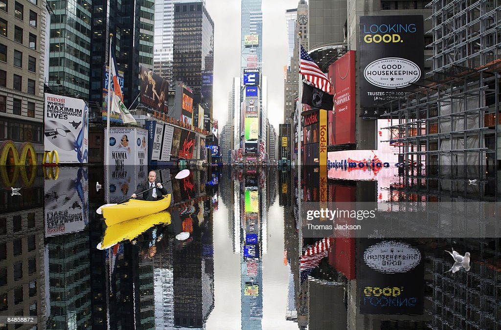 Businessman in kayak in flooded Times Square : Stock Photo