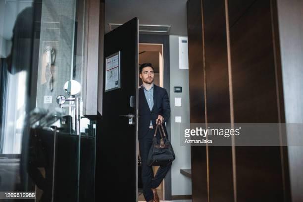 uomo d'affari alla fine degli anni '20 entrando nella camera d'albergo con i bagagli - ospite foto e immagini stock