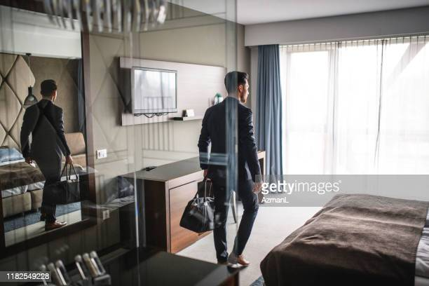 businessman in late 20s entering modern hotel room with bag - entering stock pictures, royalty-free photos & images