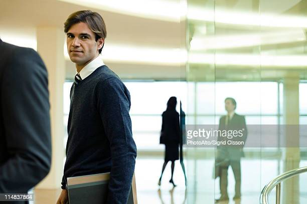 businessman in lobby, portrait - incidental people stock pictures, royalty-free photos & images