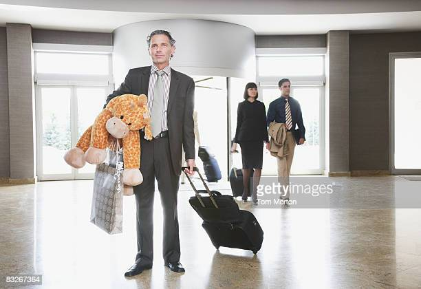 Businessman in lobby with suitcase and stuffed animal