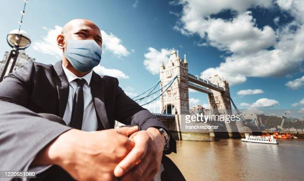 businessman in london with mask resting agains tower bridge - corona landmarks stock pictures, royalty-free photos & images