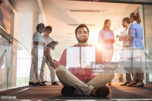 Businessman in lotus position meditating in hallway with eyes closed.