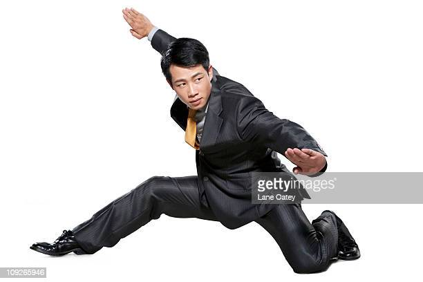 businessman in martial arts crouching stance - kung fu stock photos and pictures