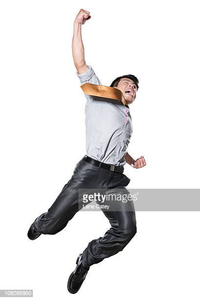 Businessman in martial arts position mid-air