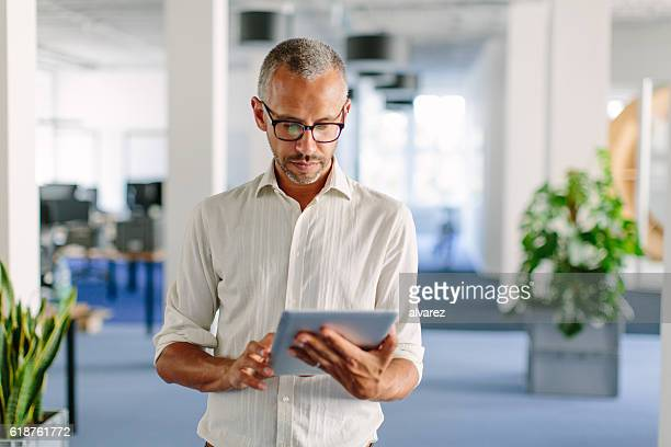 Businessman in modern office space using digital tablet