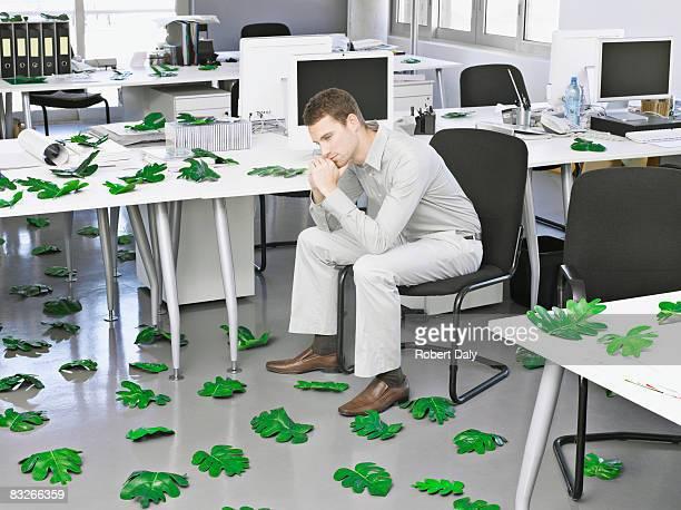 Geschäftsmann in modernen Büro umgeben von Blätter