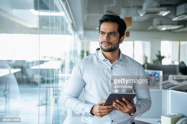 businessman in modern office with tablet - indian subcontinent ethnicity stock pictures, royalty-free photos & images