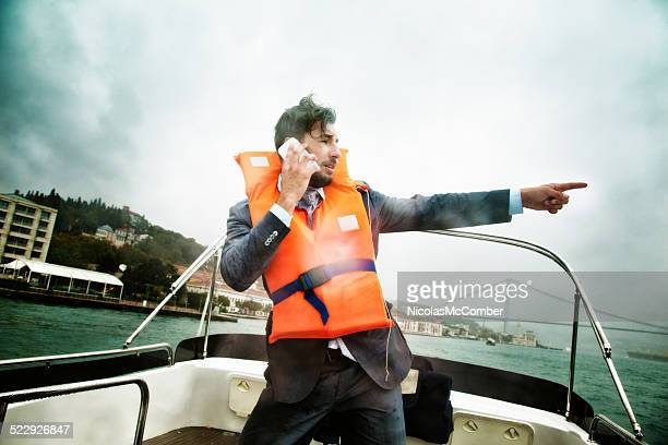 Businessman in nautical peril points towards salvation phone in hand