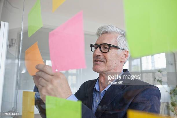 Businessman in office attaching adhesive notes at glass pane