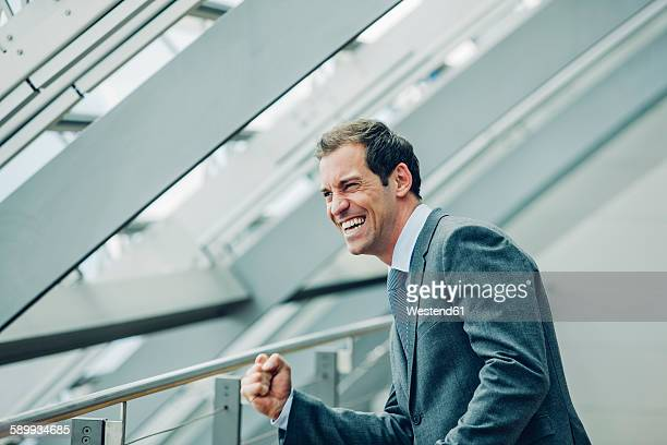 Businessman in office building cheering, celebrating success