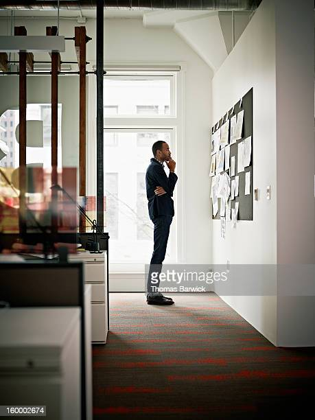 Businessman in office examining project on board