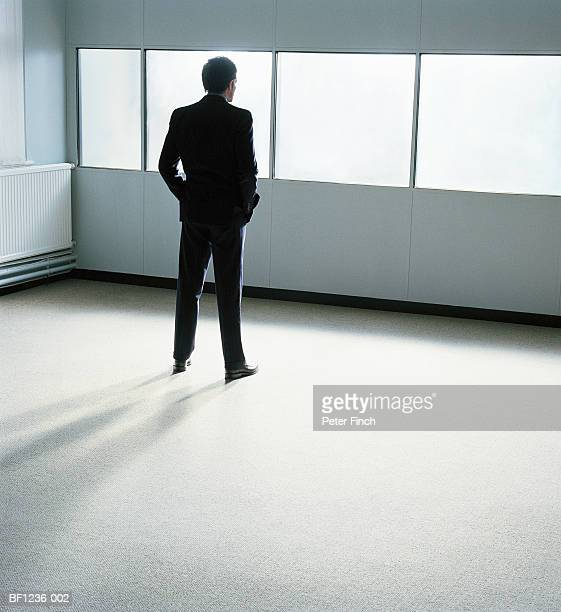 Businessman in office, hands in pockets, rear view