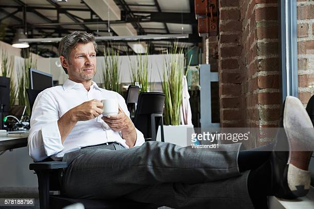 Businessman in office having a coffee beak