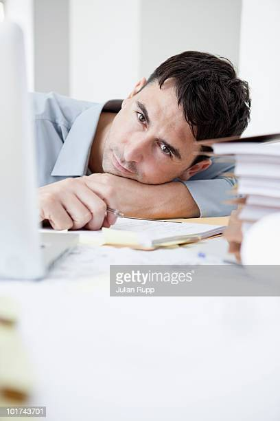 Businessman in office, head resting on hand, portrait