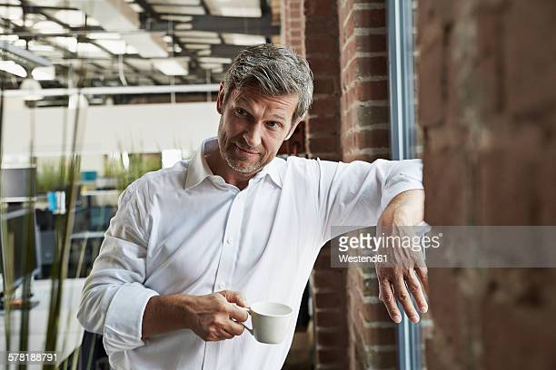 Businessman in office holding cup of coffee