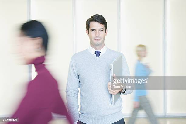 Businessman in office holding laptop with co-workers going by