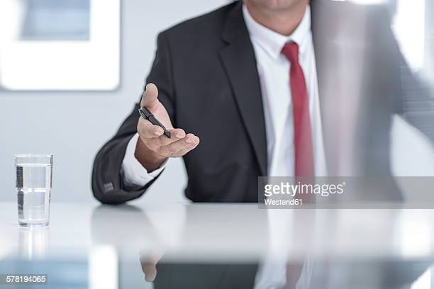 businessman in office holding pen in hand, mid section - request stock pictures, royalty-free photos & images