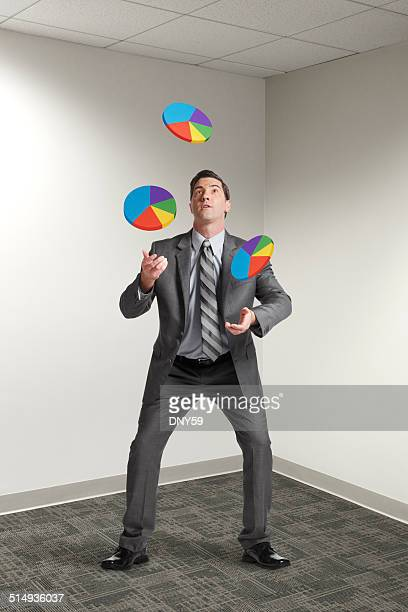 Businessman in office juggling small pie charts