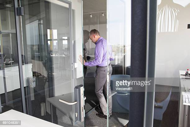 Businessman in office leaning against glass wall