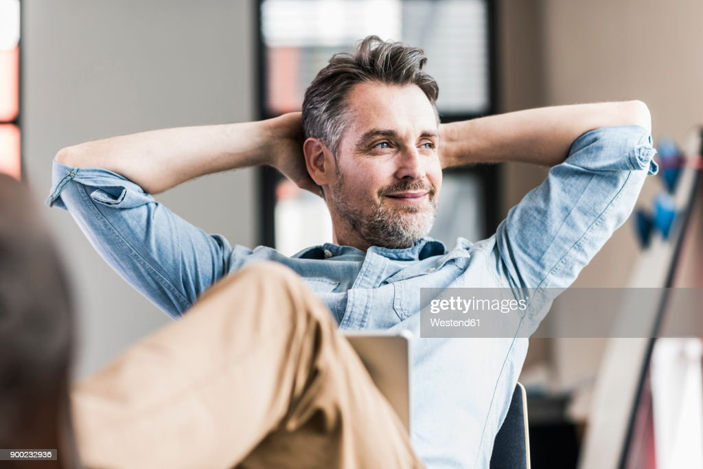 Businessman in office leaning back : Stock-Foto