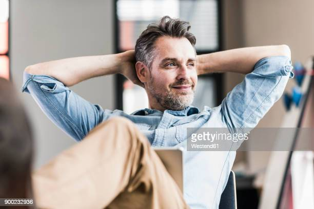 businessman in office leaning back - contente imagens e fotografias de stock