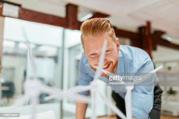 businessman in office looking at models of wind turbines - alternative energy stock photos and pictures