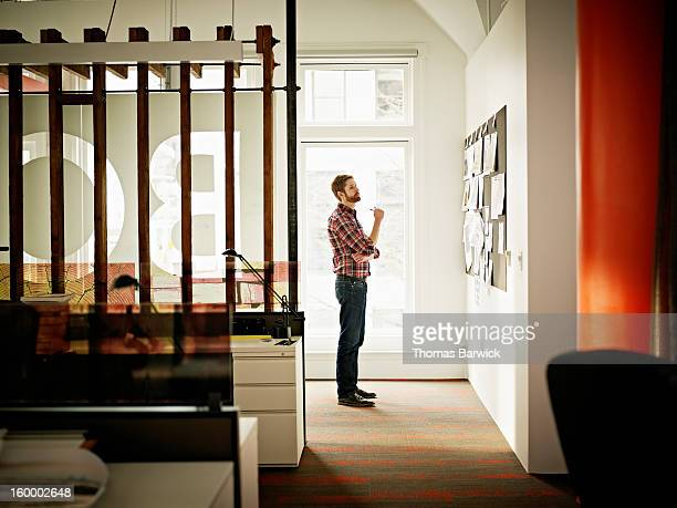 Businessman in office looking at project on board